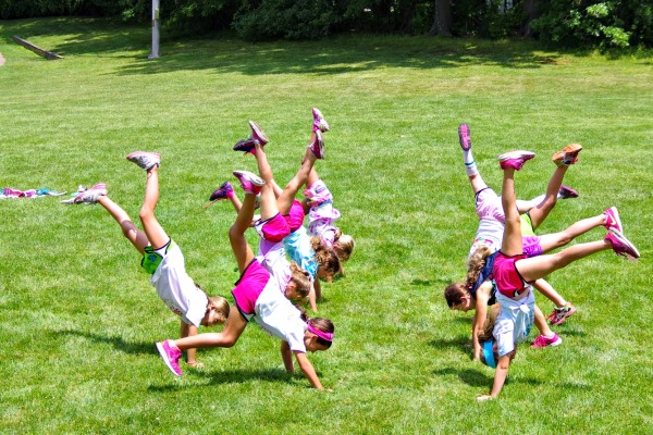 Girls having fun doing handstands at Sum It Up Lacrosse