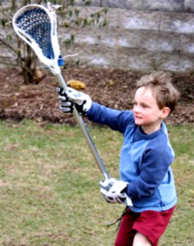 Young boy playing catch with lacrosse stick