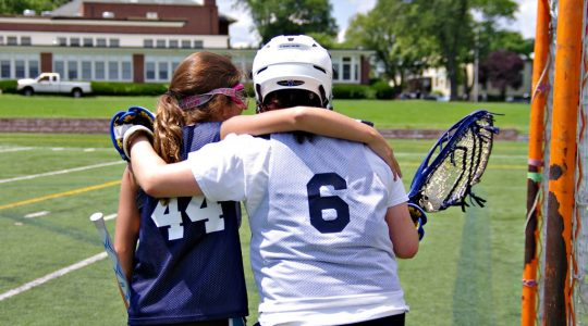 lacrosse goalie and lacrosse player supporting each other
