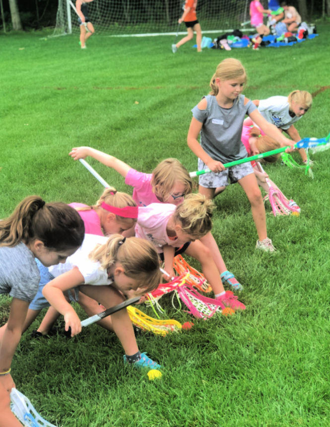 Girls scooping lacrosse balls at Swax Lax Lacrosse summer camp