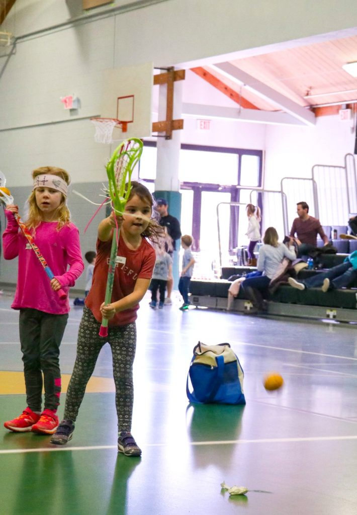 Girls playing lacrosse inside a gym at Swax Lax winter lacrosse clinics