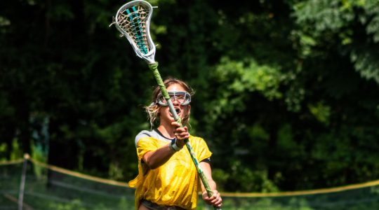Girl practicing lacrosse catching drill