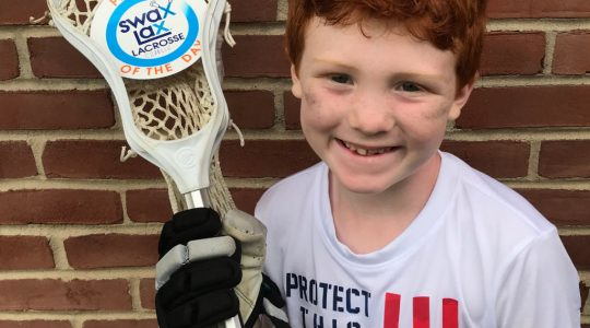 Boy earning Player of the Day sticker at Swax Lax Lacrosse summer camp